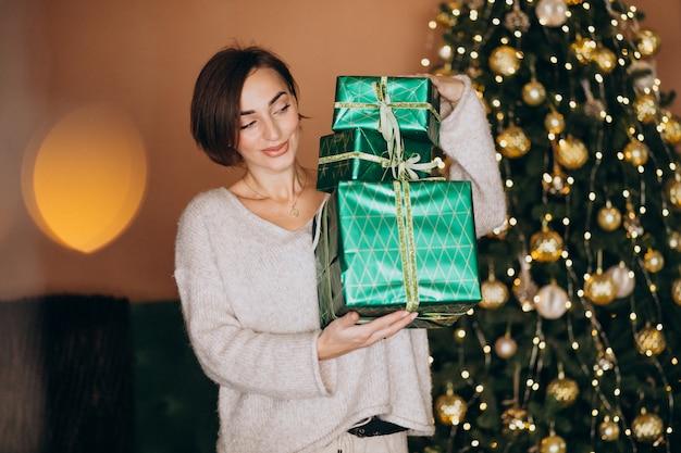Junge frau mit weihnachtsgeschenk durch den weihnachtsbaum