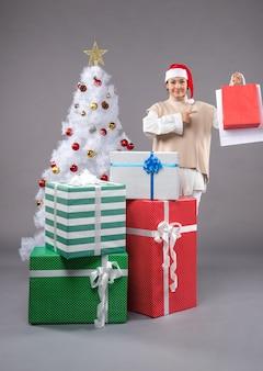 Junge frau mit weihnachtsgeschenken auf licht