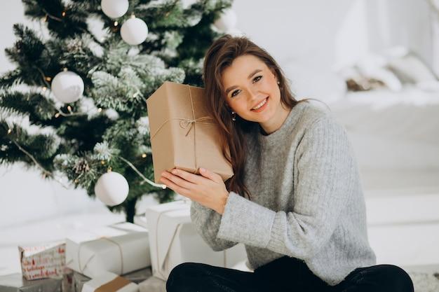 Junge frau mit weihnachtsgeschenken durch den weihnachtsbaum