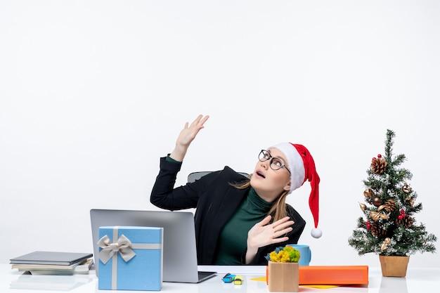 Junge frau mit weihnachtsmannhut, der an einem tisch mit einem weihnachtsbaum und einem geschenk sitzt