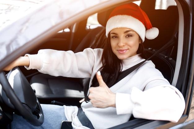 Junge frau mit weihnachtsmannhut, die ihr auto fährt