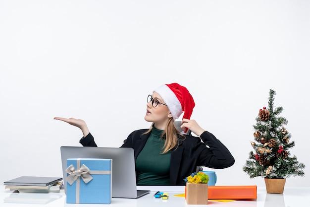 Junge frau mit weihnachtsmannhut und brille, die an einem tisch mit einem weihnachtsbaum und einem geschenk sitzen