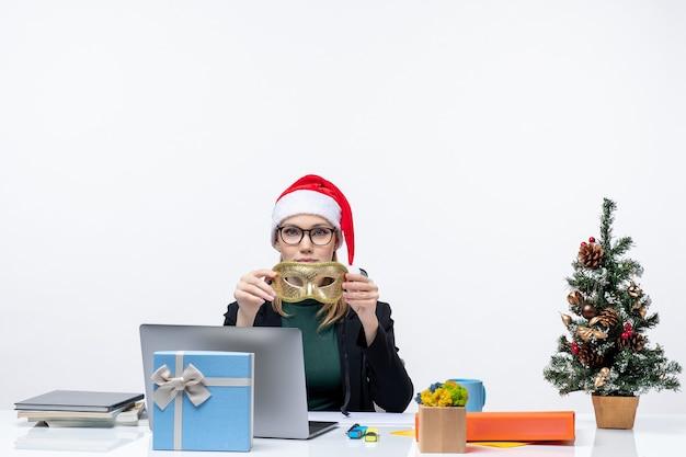 Junge frau mit weihnachtsmannhutbrille und -maske, die an einem tisch mit einem weihnachtsbaum und einem geschenk sitzt