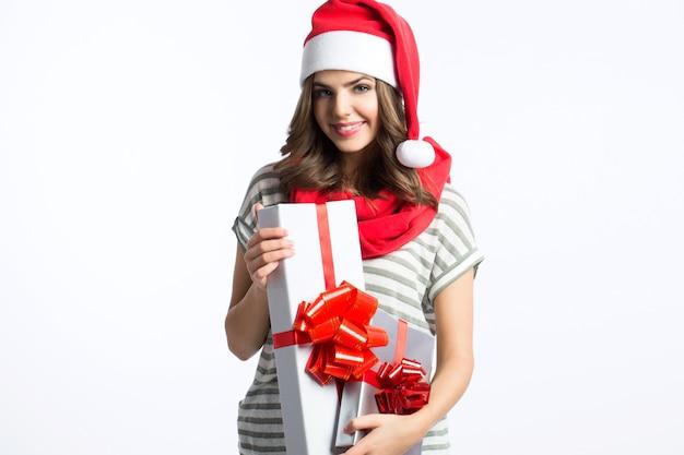 Junge frau mit weihnachtsmütze halten weihnachtsgeschenk über weißem hintergrund.
