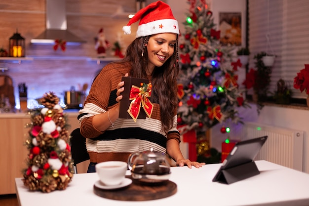 Junge frau mit weihnachtsmütze mit videoanruftechnologie