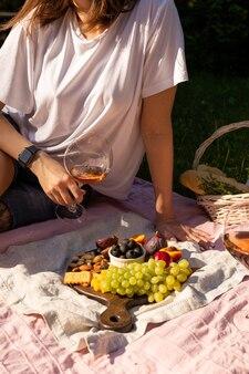 Junge frau mit weinglas bei einem sommerpicknick