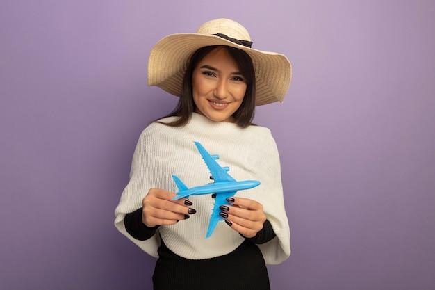 Junge frau mit weißem schal im sommerhut, der spielzeugflugzeug glücklich und fröhlich lächelnd hält