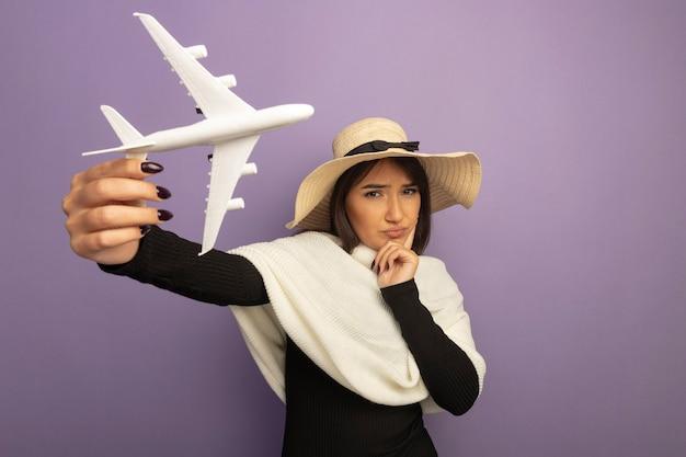 Junge frau mit weißem schal im sommerhut, der spielzeugflugzeug mit hand auf kinn denkt, das mit ernstem gesicht denkt