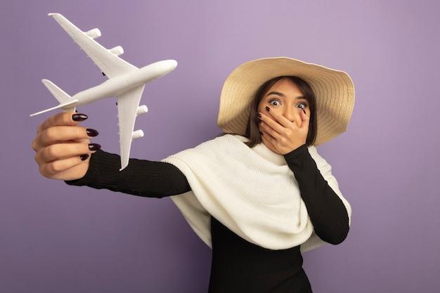 Junge frau mit weißem schal im sommerhut, der spielzeugflugzeug zeigt, das mund mit hand bedeckt