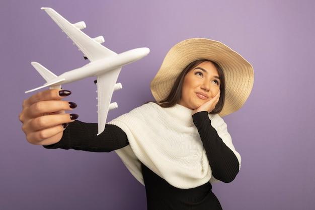 Junge frau mit weißem schal im sommerhut, der spielzeugflugzeug zeigt, das oben denkend positiv schaut