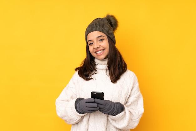 Junge frau mit winterhut isolierte gelben hintergrund, der eine nachricht mit dem handy sendet
