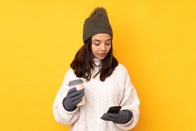 Junge frau mit winterhut über der gelben wand, die kaffee hält, um und ein mobile wegzunehmen