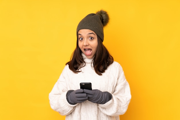 Junge frau mit winterhut über lokalisierter gelber wand überraschte und eine mitteilung sendend