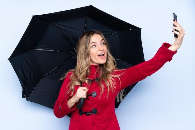Junge frau mit wintermantel, der einen regenschirm und ein handy hält