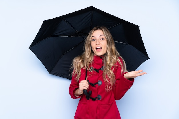 Junge frau mit wintermantel und holding ein regenschirm mit entsetztem gesichtsausdruck