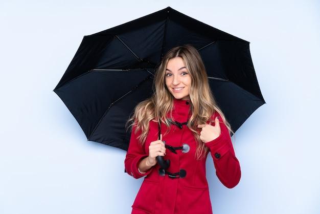 Junge frau mit wintermantel und holding ein regenschirm mit überraschungsgesichtsausdruck