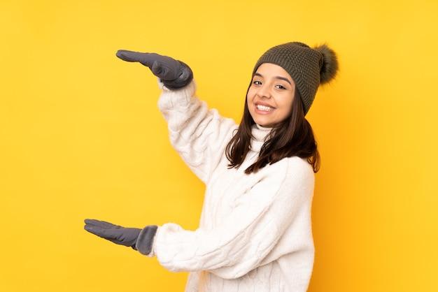 Junge frau mit wintermütze auf lokalisiertem gelbem haltekopyspace, um eine anzeige einzufügen