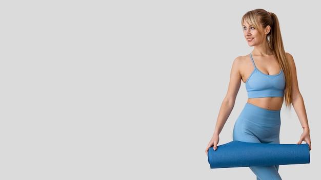 Junge frau mit yogamatte