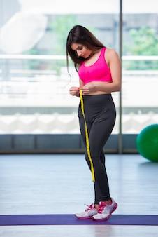 Junge frau mit zentimeter im gewichtsverlustkonzept