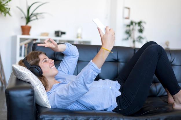 Junge frau mit ziemlich langen haaren, die auf dem rücken auf dem sofa liegt und selfie auf ihrem telefon macht