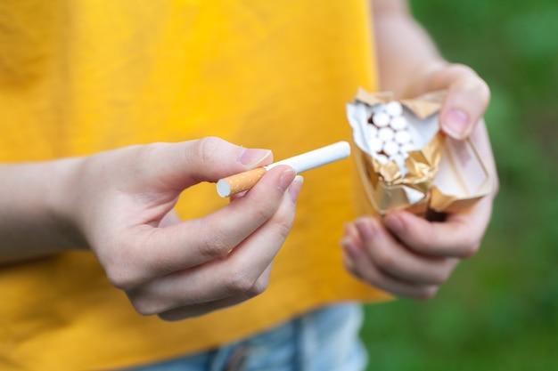Junge frau mit zigaretten in der hand, schlechte angewohnheit