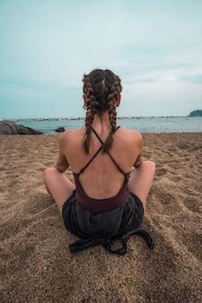 Junge frau mit zöpfen, die auf dem sand vor dem meer sitzen