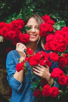 Junge frau nahe dem busch der roten rosen in einem garten