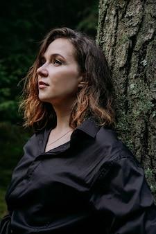 Junge frau - nahes porträt in einem dunklen kiefernwald. frau im schwarzen hemd. sie steht neben einem baum