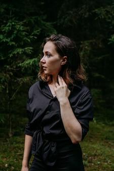 Junge frau - nahes porträt in einem dunklen kiefernwald. frau im schwarzen hemd