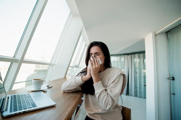 Junge frau niest in der öffentlichkeit. freiberuflerin, die im kaffeehaus an ihrem modernen laptop arbeitet, putzt sich mit papierservietten die nase. frau wurde wegen kaltem wetter draußen krank. bleiben sie zu hause, wenn sie krank sind!