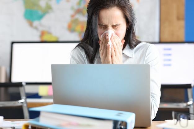 Junge frau niest in taschentuch am arbeitsplatz im büro