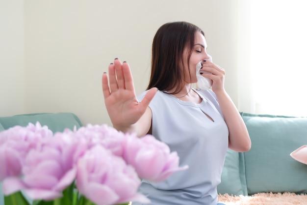 Junge frau niest von blumenallergie. pollenallergie