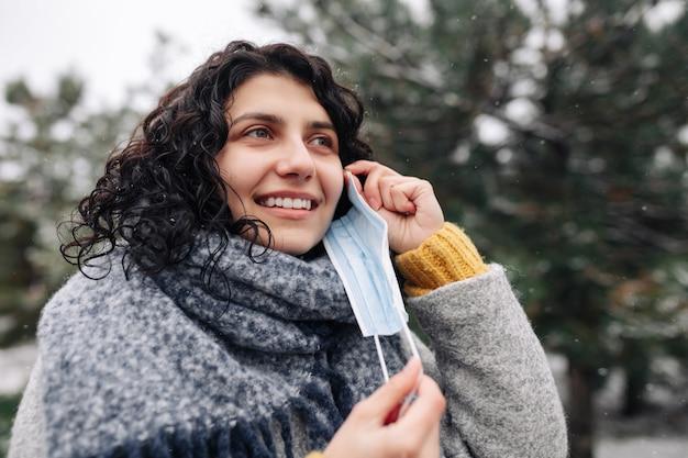 Junge frau nimmt die medizinische sterile maske in einem schneebedeckten winterpark an einem kalten frostigen tag ab.