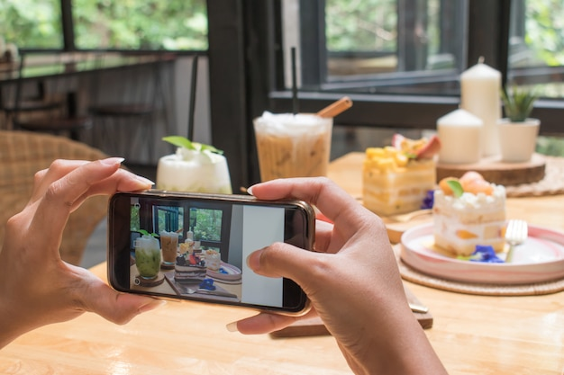 Junge frau nimmt einen kuchen mit einem smartphone im restaurant