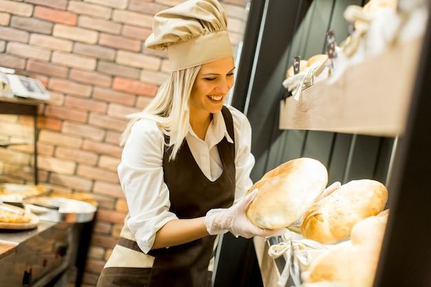 Junge frau nimmt frisches brot von den regalen in einem bäckergeschäft