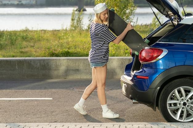 Junge frau nimmt skate vom kofferraum, um weibliche skateboardfahrer zu fahren, die longboarding im freien üben