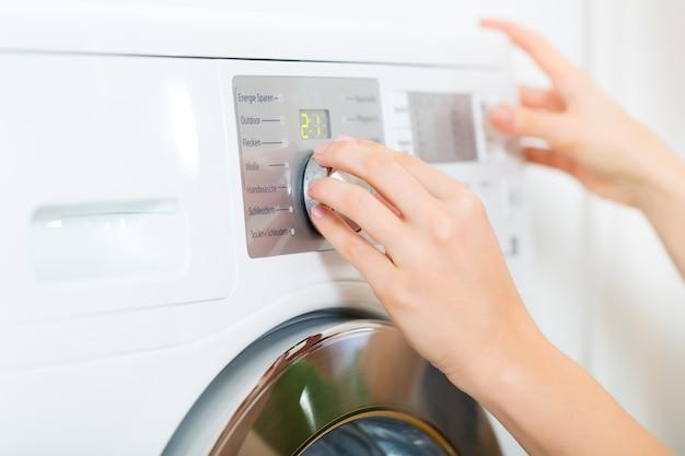 Junge frau oder haushälterin hat einen waschtag zu hause, sie wählt das programm aus