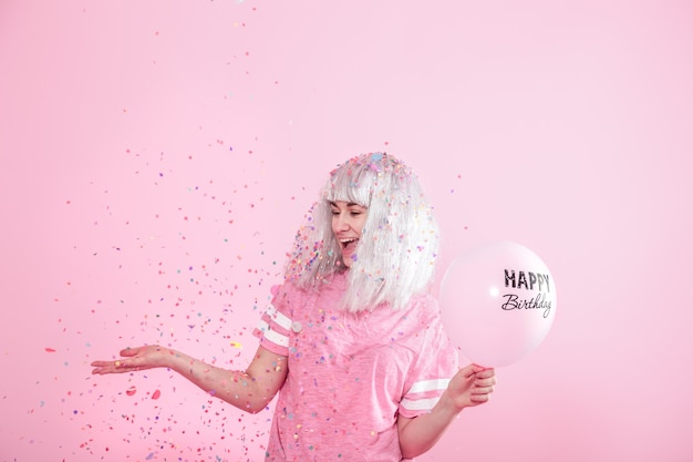 Junge frau oder mädchen mit luftballons alles gute zum geburtstag. wirft konfetti von oben. urlaubs- und partykonzept.