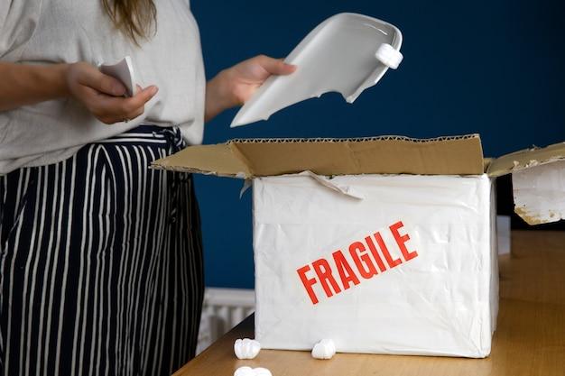 Junge frau öffnet beschädigtes lieferpaket, online-shopping-paket. zerbrochener zerbrechlicher teller zu hause