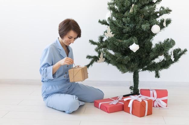 Junge frau öffnet geschenke unter weihnachtsbaumweihnachten und neujahrskonzept