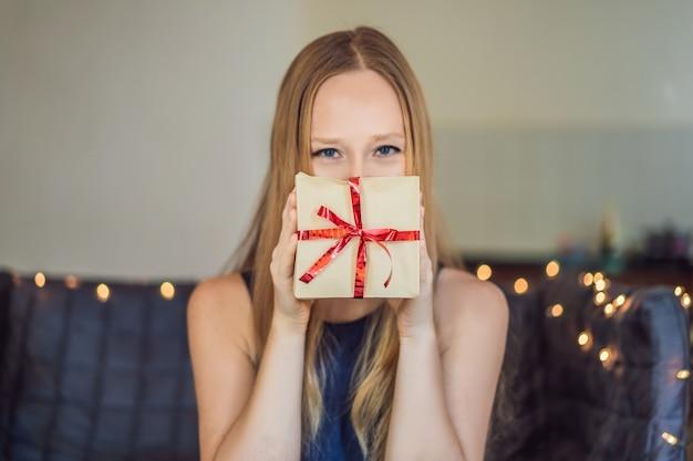 Junge frau packt geschenke. geschenk in bastelpapier mit einem rot-goldenen band für eingewickelt