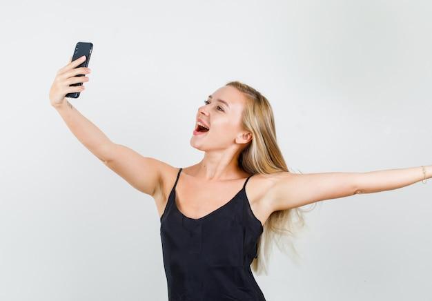 Junge frau posiert beim selfie im schwarzen unterhemd und schaut fröhlich