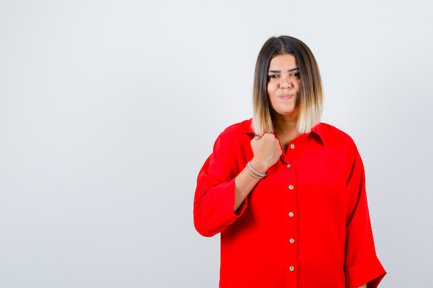 Junge frau posiert beim stehen im roten übergroßen hemd und sieht fröhlich aus. vorderansicht.