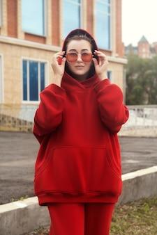 Junge frau posiert in einem roten, warmen, lässigen sportkostüm
