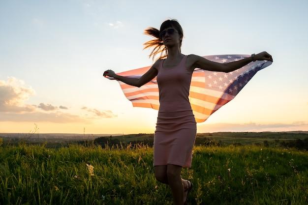 Junge frau posiert mit der nationalflagge der usa im freien bei sonnenuntergang.