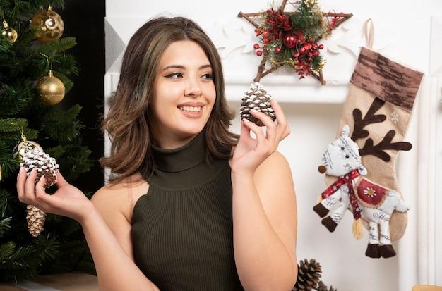 Junge frau posiert mit tannenzapfen in der nähe des weihnachtsbaums