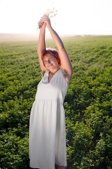 Junge frau posiert selbstbewusst im freien auf einem feld und zeigt achselhaare