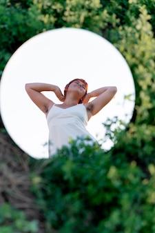 Junge frau posiert selbstbewusst im freien mit einem runden spiegel