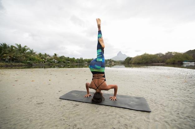 Junge frau praktiziert yoga am ufer des indischen ozeans in mauritius