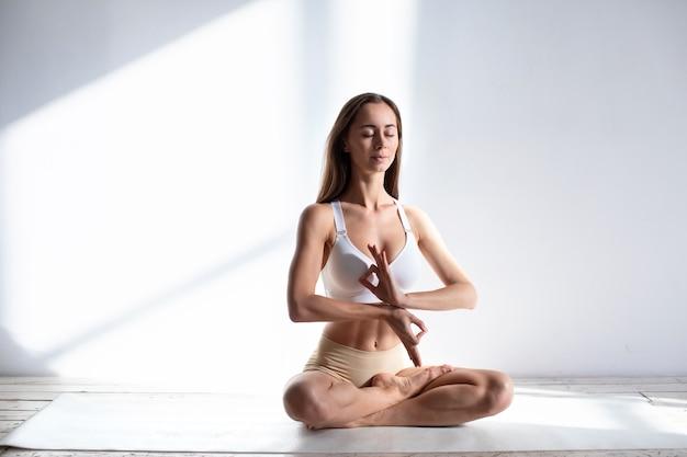 Junge frau praktiziert yoga im studio auf einem weißen hintergrund. namaste-konzept.